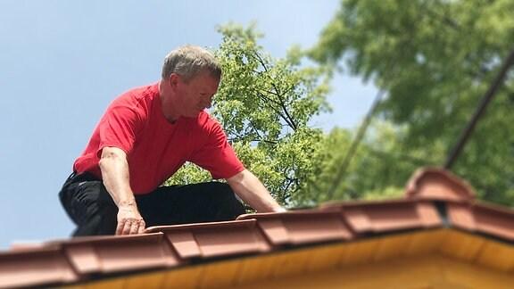 Ein Dachdecker auf einem Hausdach