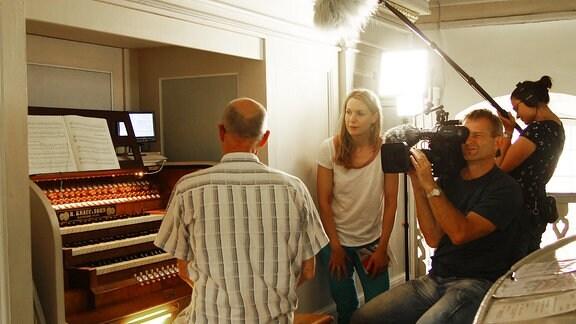 Ein Kamerateam filmt einen Organisten an seinem Instrument