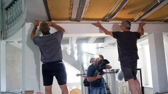 Handwerker dämmen eine Kirchenzwischendecke