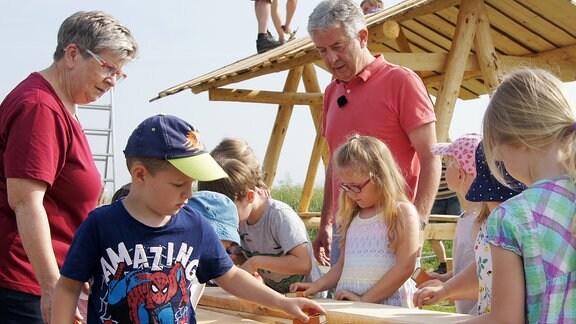 Kinder und Erwachsene arbeiten mit Schleifpapier an einem Holz-Picknick-Tisch