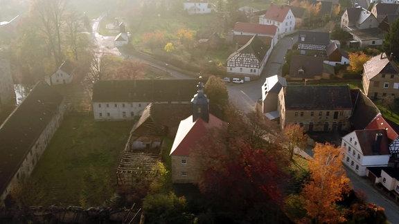 Luftaufnahme des OrtesDobitschen. Im Vordergrund eine Kirche und weitere Gebäude.