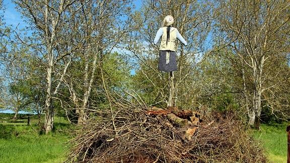 Ein Holzhaufen mit einer Hexenpuppe darauf