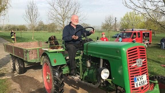 Ein Mann fährt Traktor, auf dem Beifahrersitz sitzt ein Langhaardackel
