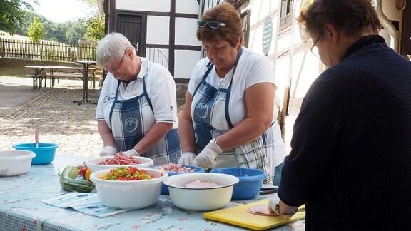 Frauen schneiden Zutaten für Wurstsalat.