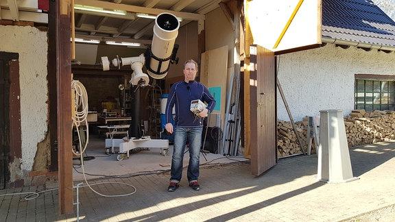 Ein Riesen-Teleskop steht in einer Garage. Es ist größer als der Mann der davor steht.
