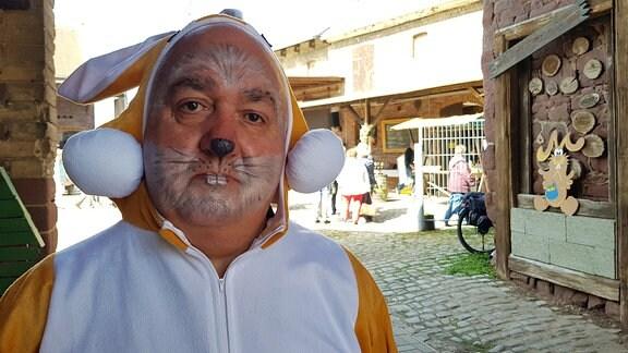 Porträt eines Mannes, der als Osterhase verkleidet und geschminkt ist.
