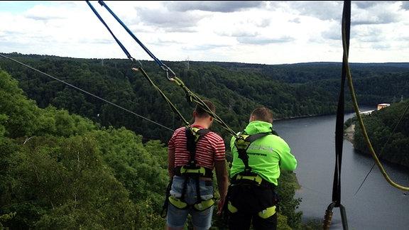 Zwei Männer sind mit Seilen gesichert und blicken auf die Rappbodetalsperre.