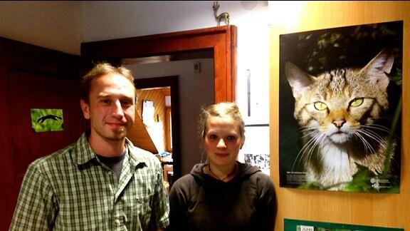 Ein junger Mann und eine junge Frau vor Tierbildern