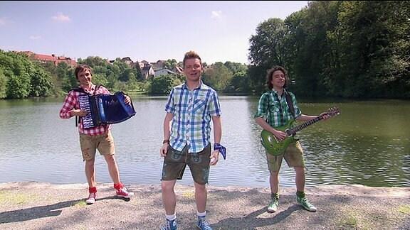 drei junge Musiker vor einem See