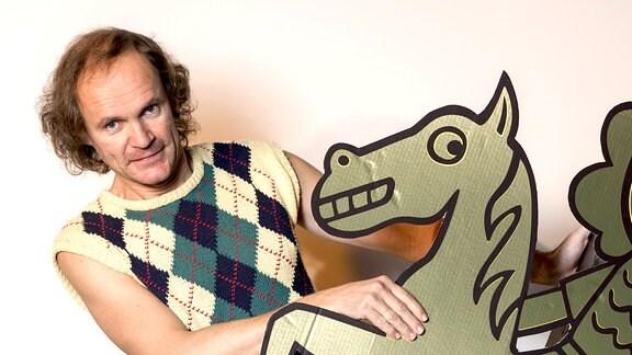 """Schirmherr Olaf Schubert mit dem Logo der """"Humorzone Dresden"""""""