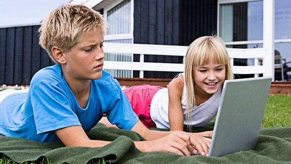 Kinder mit Laptop liegen vor einem Holzhaus auf einer Wiese