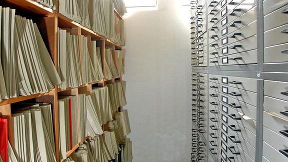 Ein Gang in einem Archiv; links ein Regal mit Akten, rechts ein Regal mit Schubfächern