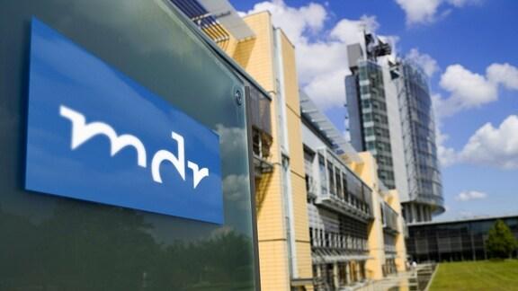 Das Logo des Mitteldeutschen Rundfunks und im Hintergrund das Hochhaus
