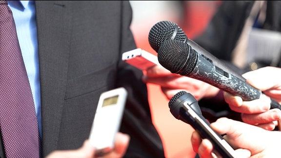 Mikrofone und Aufnahmegeräte werden einem Mann hingehalten