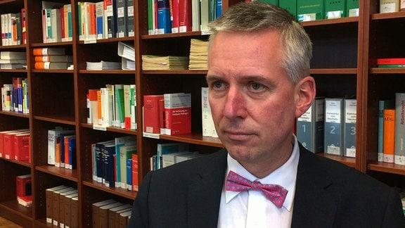 Ein Mann steht vor einem Bücherregal