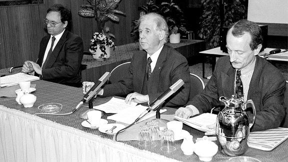 Drei Männer sitzen an einem Tisch. Vor ihnen stehen Mikrofone