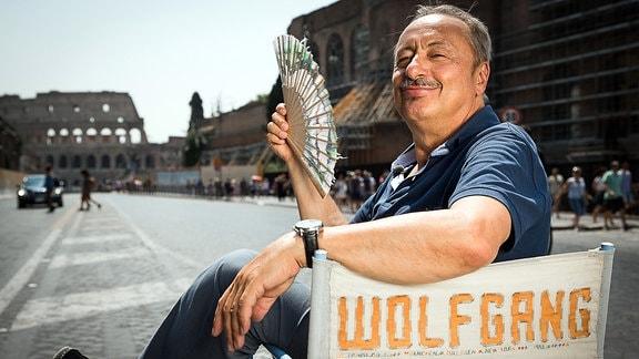 """Schauspieler Wolfgang Stumph sitzt mitten in Rom auf der Via dei Fori Imperiali mit Blick auf das Kolosseum auf einen Regiestuhl mit der Aufschrift """"Wolfgang"""""""