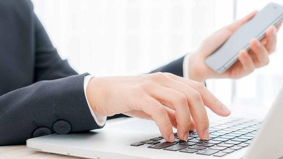 Eine Person sitzt am Laptop und hält in einer Hand ein Handy.