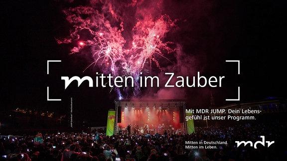 Tausende Menschen bei einem Konzert sehen ein Feuerwerk direkt hinter der Bühne
