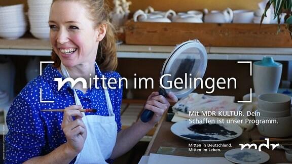eine junge Frau sitzt in einer Töpferwerkstatt  und schaut lachend auf, während sie ein zu bemalendes Objekt und einen Pinsel in der Hand hält