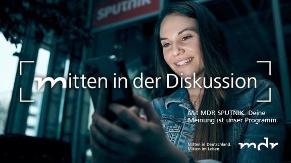 Eine junge Frau mit schwarzen Haar hält ein Smartphone in beiden Händen. Das Licht des Bildschirms erhellt ihr Gesicht.