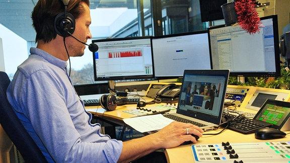Redakteur im Gespräch mit mehreren Teilnehmern via Webcam auf Laptopbildschirm. .