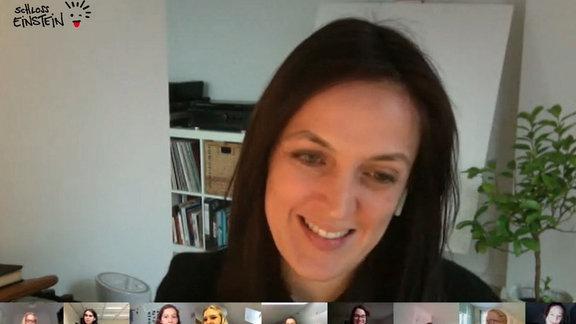 Eine Frau lächelt in die Kamera, darunter sind kleine Live-Bilder weiterer Menschen zu sehen.