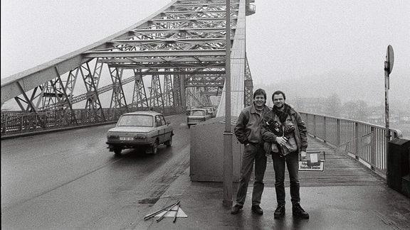 """Schwarzweißaufnahme vom Filmemacher Wolfgang Ettlich und der Kameramann Hans-Albrecht Lusznat im Januar 1990 in Dresden vor dem """"Blauen Wunder""""."""
