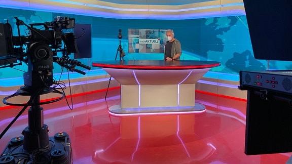 Ein Mann mit Mund-Nasen-Schutz steht im TV-Studio hinter einem Pult. Vor ihm steht eine Kamera.