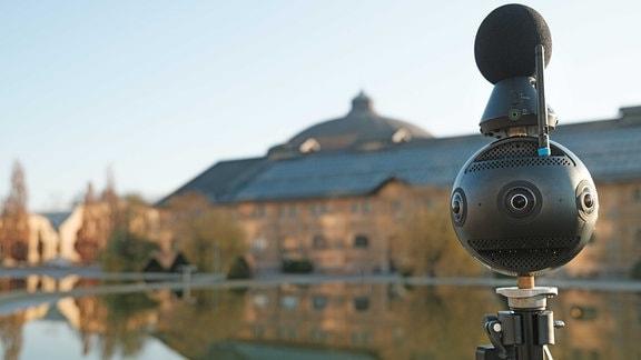 360-Grad-Kamera steht vor einem Teich, in dem sich ein Gebäude spiegelt