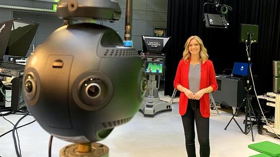Eine blonde Frau in rotem Sakko lächelt in eine 360-Grad-Kamera