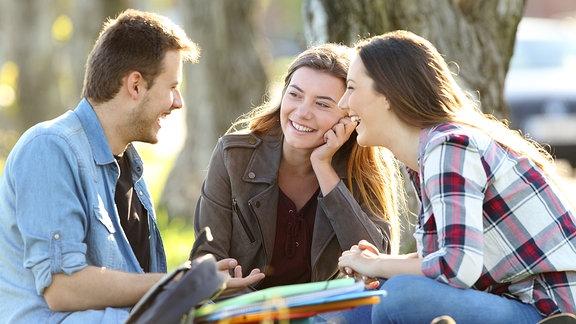 Ein junger Mann und zwei junge Frauen sitzen im Park und lachen
