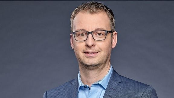 Ein Mann mit kurzen Haaren und Brille lächelt in die Kamera