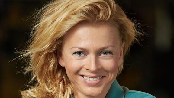 Eine blonde Frau mit schulterlangem Haar lächelt in die Kamera