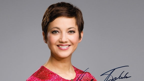 Eine Frau mit kurzen, dunkelbraunen Haaren lächelt.