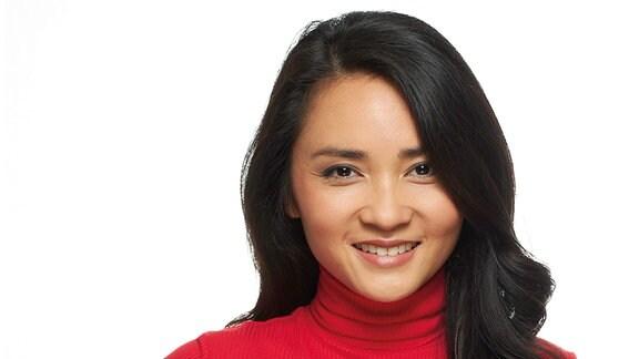Eine Frau mit langem schwarzen Haar und rotem Rollkragenpullover lächelt.