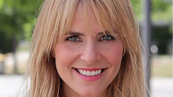 Eine junge Frau mit langem blonden Haar lächelt in die Kamera.