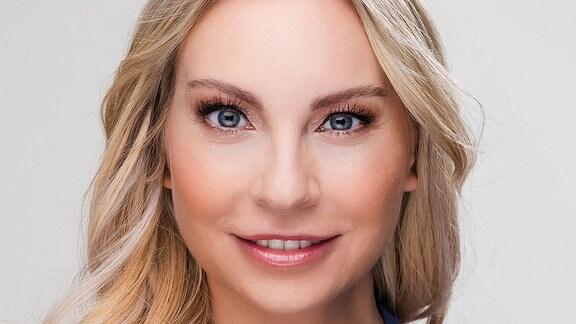 Eine Frau mit langem, blodem Haar lächelt in die Kamera