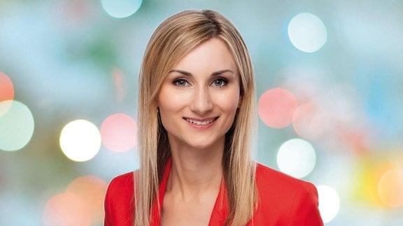Eine jung Frau mit langem Haar und roter Jacke lächelt in die Kamera