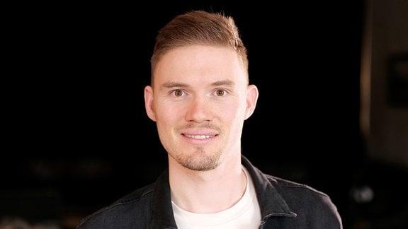 Ein Mann mit Drei-Tage-Bart lächelt in die Kamera