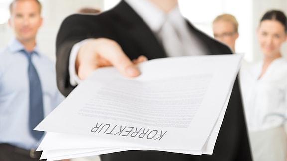 """Einer Gruppe von Geschäftsleuten zeigt ein junger Mann schriftliche Unterlagen mit der Aufschrift """"Korrekturen""""."""