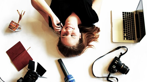 Eine junge Frau liegt telefonierend und von allerlei Arbeitsutensilien umgeben auf dem Boden.