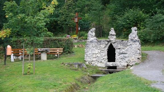 Eine Art steinernes Tor mit Türmchen und eine Holzbank stehen zwischen Bäumen