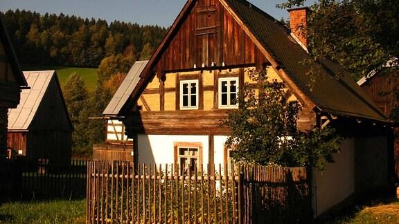 Ein kleines Fachwerkhaus steht auf einer Wiese mit einem Waldstück am Horizont