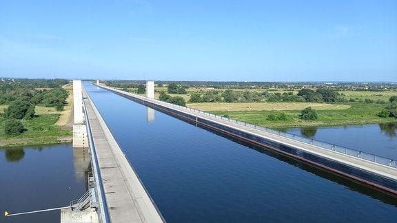 Eine Brücke voller Wasser führt über einen Fluss
