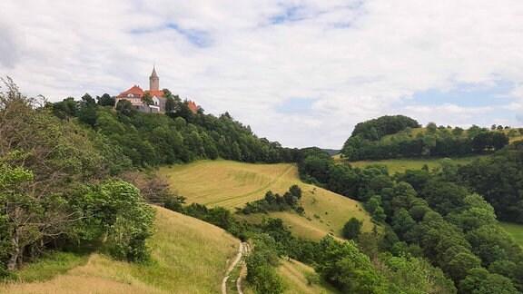 Auf der Spitze einer hügeligen, grünen Landschaft befindet sich ein Dorf mit Kirchturm