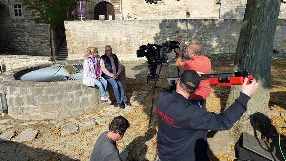 Vici und Andreas sitzen in einem Hof, umringt vom MDR-Kamerateam