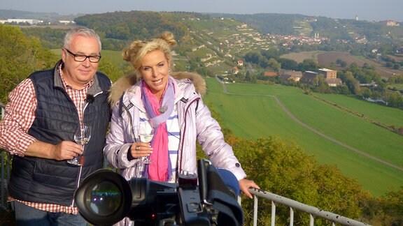 Vici und Andreas stehen vor traumhafter Kulisse einen Weinanbaugebiets mit einem Weinglas in der Hand
