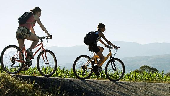 Mädchen fahren im Gebirge Rad