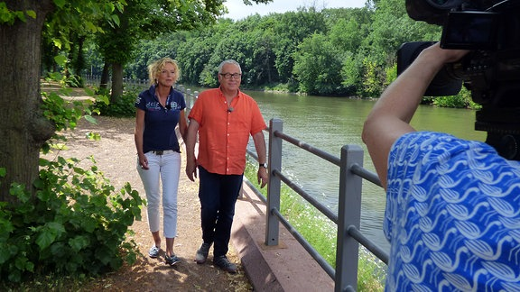 Die Unterwegs-Moderatoren Victoria Herrmann und Andreas Neugeboren laufen entlang der Saale und werden dabei gefilmt